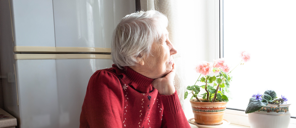 older woman sitting at window staring out
