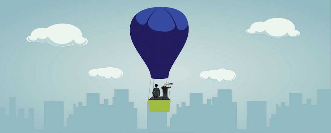 Balloon with 2 men lifting up above city scape