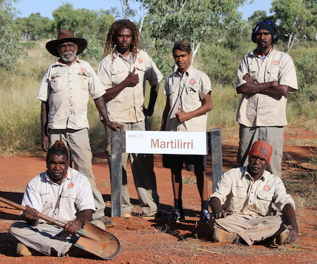 Group of Indigenous men with uniform shirts standing around a sign for Well 22 Martilirri on Canning Stock Route