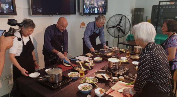 group of older people preparing food in a cooking class being filmed